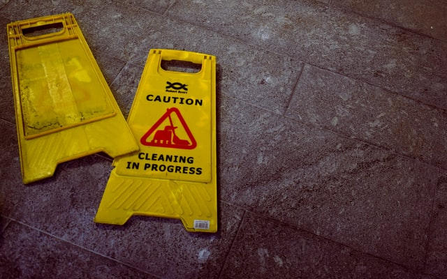 : A yellow caution sign on a floor stating cleaning in progress.