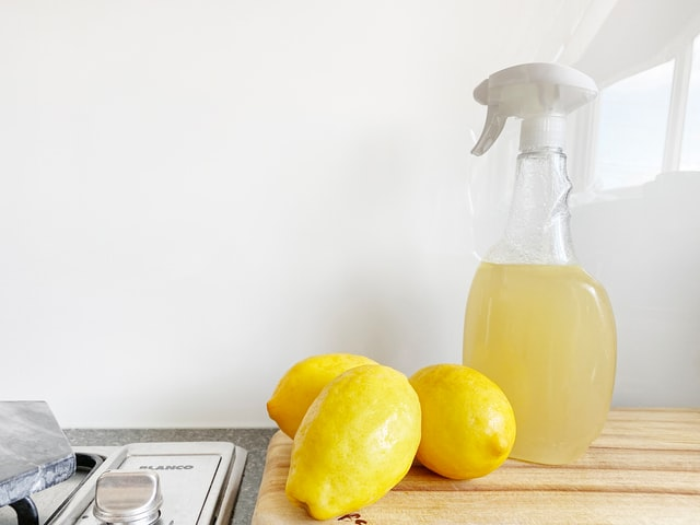 Three lemons and lemon spry on the kitchen counter.