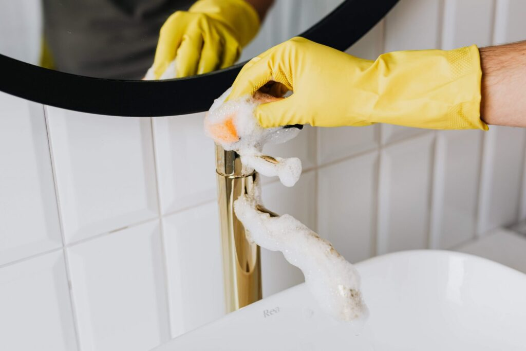 A professional cleaner in yellow gloves, cleaning a tap in the bathroom