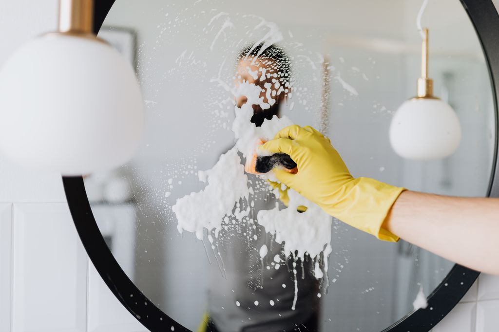 A man cleaning a mirror