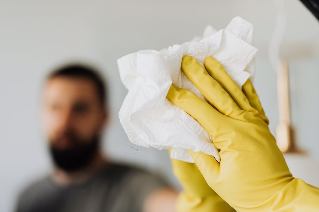 A person in yellow gloves cleaning, symbolizing the difference between a deep cleaning and a maintenance cleaning