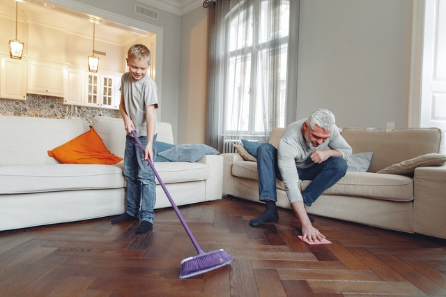 a man and a boy spring cleaning the floor with a broom and a cloth