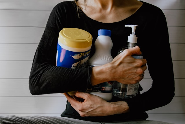 A woman holding cleaning products