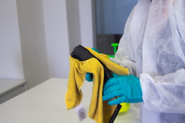 A person in a uniform disinfecting and cleaning a post rental because of the pandemic.