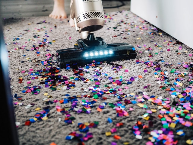 A vacuum cleaner cleaning a messy rug.