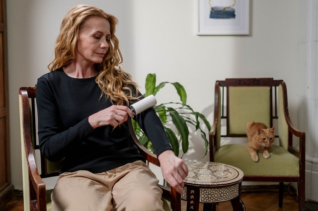 A woman using a lint roller which is one of the excellent cleaning tips for pet owners