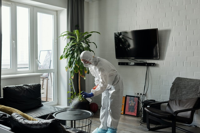 A man in protective gear cleaning a living room table.